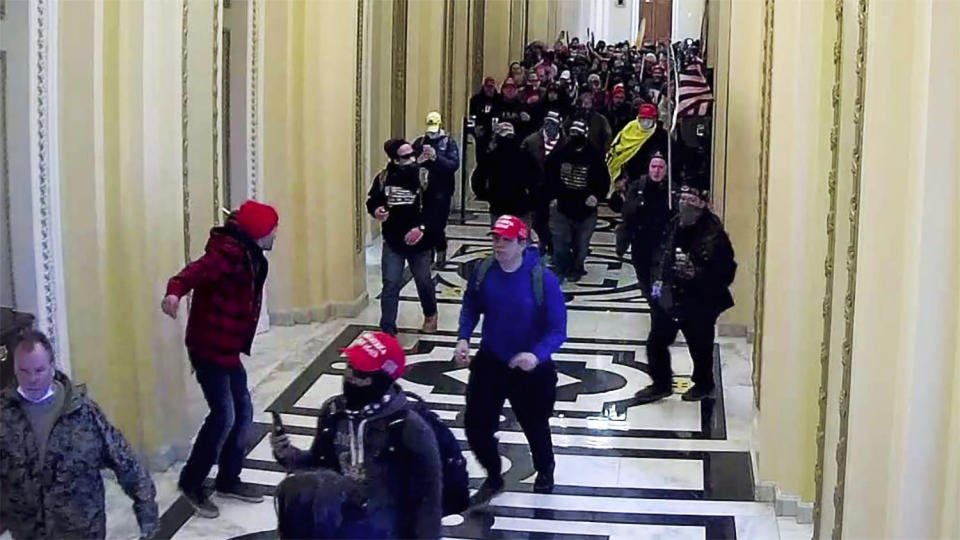 In this image taken from video footage released in a criminal complaint by the U.S. District Court for the District of Columbia, Alexander Sheppard, center, joins other rioters who stormed the U.S. Capitol on Jan. 6, 2021, in Washington. Sheppard, of Ohio, was arrested Tuesday, Feb. 23, in connection with the deadly insurrection after being identified by an acquaintance to the FBI, according to U.S. District Court documents. (U.S. District Court for the District of Columbia via AP)