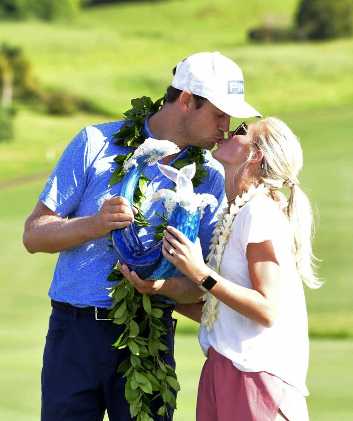 Harris English kisses his wife, Helen English, as he holds the champions trophy after the final round of the Tournament of Champions golf event, Sunday, Jan. 10, 2021, at Kapalua Plantation Course in Kapalua, Hawaii. (Matthew Thayer/The Maui News via AP)