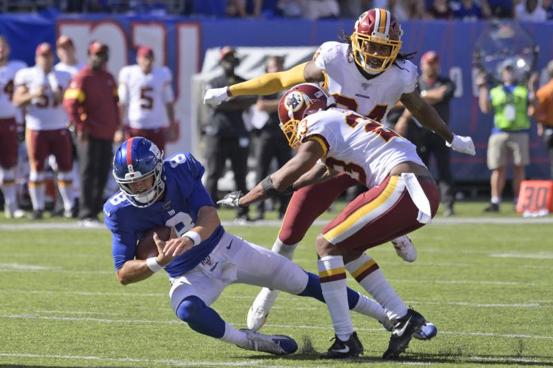 New York Giants quarterback Daniel Jones, left, dives through Washington Redskins defenders during the second half of an NFL football game, Sunday, Sept. 29, 2019, in East Rutherford, N.J. (AP Photo/Bill Kostroun)
