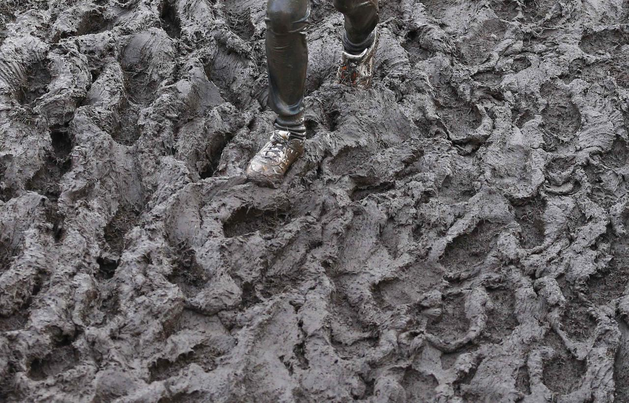 A competitor runs through mud during the Tough Guy event in Perton, central England, January 26, 2014. The annual event to raise cash for charity challenges thousands of international competitors in a cross country run followed by an assault course consisting of obstacles including water, fire and tunnels. REUTERS/Darren Staples (BRITAIN - Tags: SPORT ATHLETICS SOCIETY)