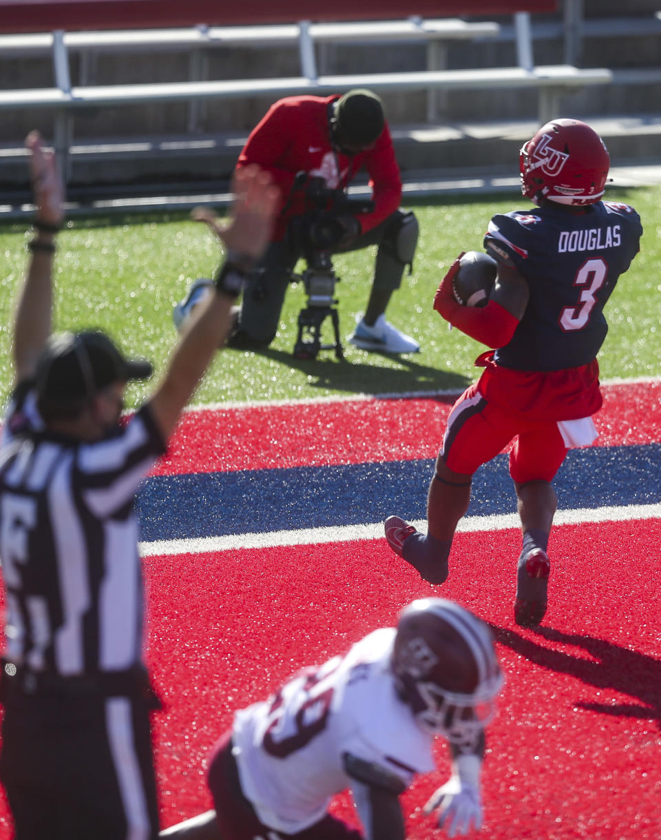 Liberty wide receiver Demario Douglas (3) scores a touchdown as he is defended by Massachusetts player Cody Jones (29) during the first half of an NCAA college football game on Friday, Nov. 27, 2020, at Williams Stadium in Lynchburg, Va. (AP Photo/Shaban Athuman)