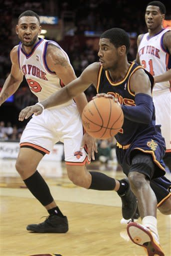 Cleveland Cavaliers' Kyrie Irving (2) drives past New York Knicks' Jared Jeffries (9) in the second quarter in an NBA basketball game on Wednesday, Jan. 25, 2012, in Cleveland. (AP Photo/Tony Dejak)