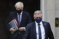 "Britain's Prime Minister Boris Johnson, left, leaves Downing Street with a member of security staff to attend the weekly session of Prime Ministers Questions at Parliament in London, Wednesday, Oct. 21, 2020. The European Union is taking a defiant tone as the standoff over resuming post-Brexit trade negotiations with the United Kingdom continues. The bloc told London Wednesday that ""you cannot have your cake and eat it too."" (AP Photo/Frank Augstein)"