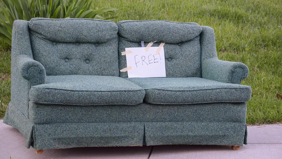 A sofa placed on the sidewalk with a sign marking it free for pick up.