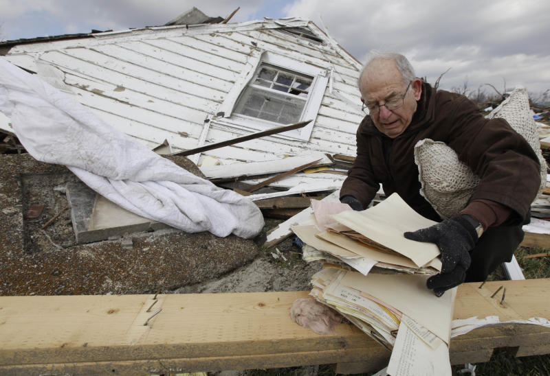 Tasos Pantelidis search search through a home destroyed by a tornado in Marysville, Ind., Sunday, March 4, 2012. Calm weather gave dazed residents of storm-wracked towns a respite on Sunday as they dug out from a chain of tornadoes that cut a swath of destruction from the Midwest to the Gulf of Mexico, killing at least 39 people. (AP Photo/Nam Y. Huh)