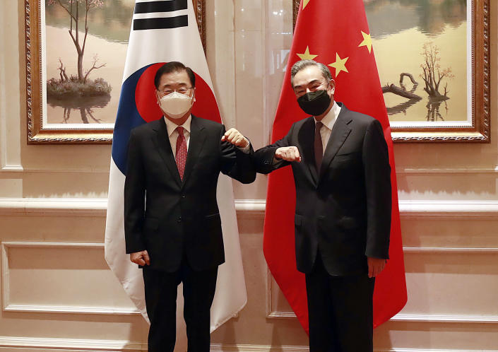 South Korean Foreign Minister Chung Eui-yong, left, and Chinese Foreign Minister Wang Yi bump elbows prior to their meeting in Xiamen, China, Saturday, April 3, 2021. South Korea's foreign minister met his Chinese counterpart in the southern Chinese city of Xiamen on Saturday, as Seoul seeks to improve ties with its top trading partner even as U.S.-China relations remain strained. (Kim Yun-gu/Yonhap via AP)