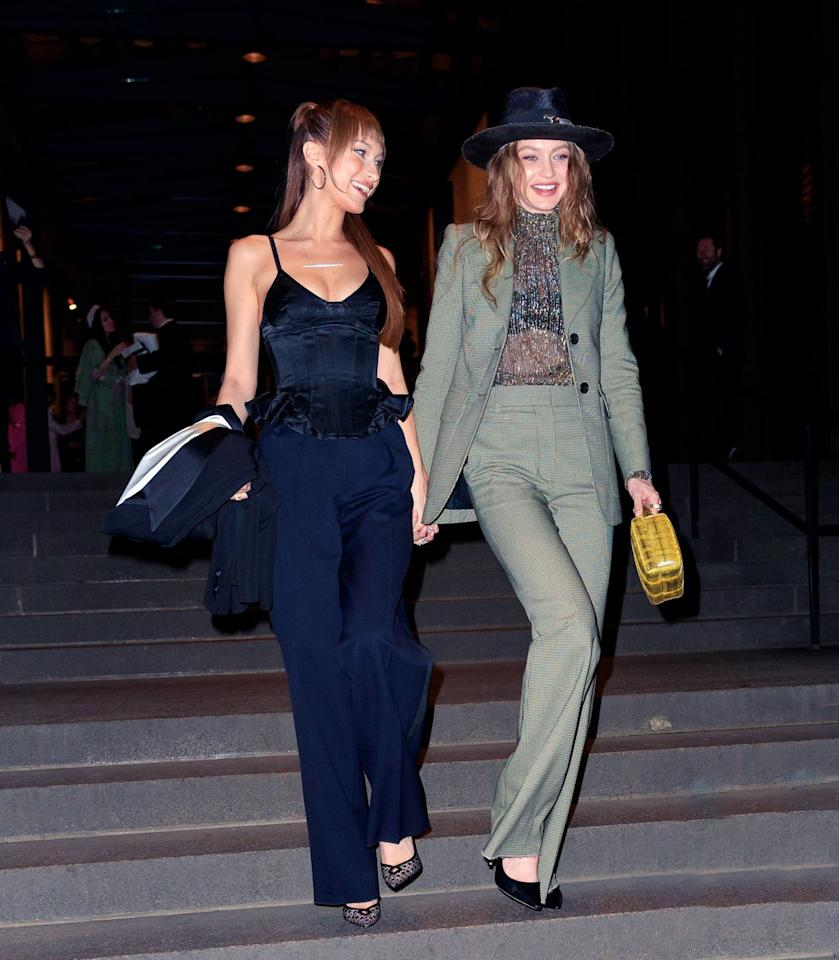 <p>For Marc Jacobs' wedding in NYC, the Hadid sisters went with smart suited ensembles. While Bella opted for a peplum top and navy trousers, Gigi wore a gray two-piece suit with a sheer high-neck top that showed off her bra. She topped it off with a Youssef Lahlou hat. A yellow python-print bag added a pop of color. </p>