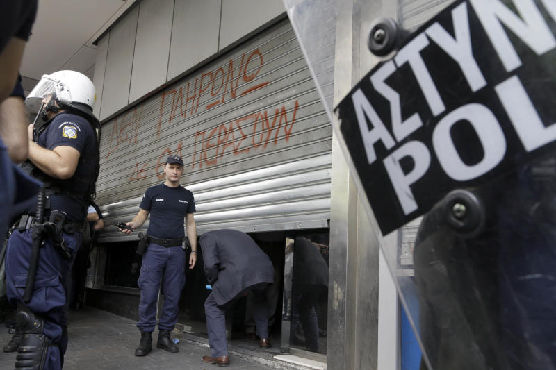 "Riot police stand by as a man ducks under lowered shutters at the entrance of the finance ministry, in Athens on Thursday, Oct. 11, 2012. Writing on the shutters reads: ""We won't pay. This will not pass."" High school children protested outside the ministry Thursday against state funding cuts to municipalities that have disrupted school bus services. Greece's coalition government is struggling to meet demands by international rescue creditors for a massive new austerity cuts required for continued payment of emergency loans. (AP Photo/Dimitri Messinis)"