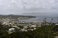The Royal Caribbean cruise ship Reflection sits docked waiting to evacuate a group of British, Canadian and U.S. nationals in Kingstown, on the eastern Caribbean island of St. Vincent, Friday, April 16, 2021. La Soufriere volcano has shot out another explosive burst of gas and ash Friday morning as the cruise ship arrived to evacuate some of the foreigners who had been stuck on a St. Vincent island by a week of violent eruptions. (AP Photo/Orvil Samuel)