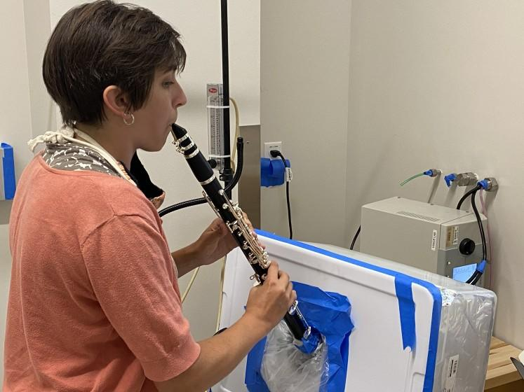 Researcher Tehya Stockman plays a clarinet in a University of Colorado Boulder lab to measure aerosol output.