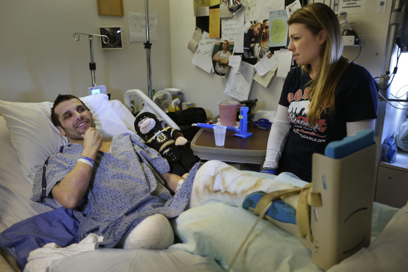 In this Thursday, May 9, 2013 photo, Marc Fucarile, left, jokes while speaking with members of the media as his fiancee, Jennifer Regan, right, looks on in his room at Massachusetts General Hospital in Boston. Fucarile was only feet away from a bomb blast Monday, April 15 near the finish line of the Boston Marathon that resulted in the loss of one leg, severe damage to the other, as well as burns, and a piece of shrapnel lodged in his heart. (AP Photo/Steven Senne)