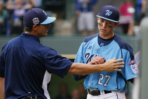 Las Vegas' Brennan Holligan (27) is comforted by manager Aston Cave, left, as he returns to the dugout after reaching his pitch limit in the fifth inning of a United States Championship game against Chicago at the Little League World Series tournament in South Williamsport, Pa., Saturday, Aug. 23, 2014. Chicago won 7-5. (AP Photo/Gene J. Puskar