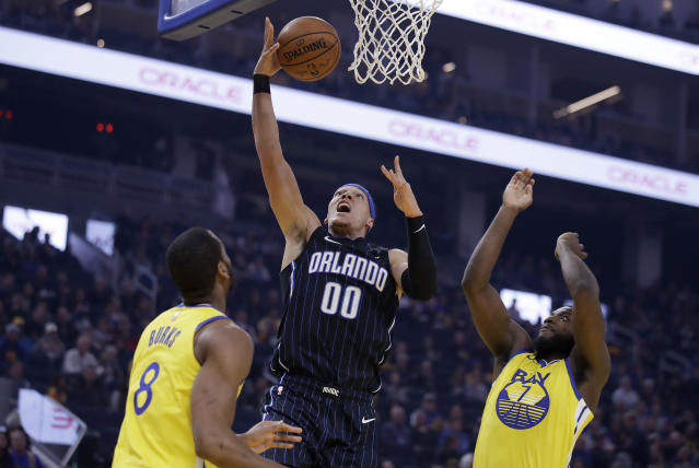 Orlando Magic's Aaron Gordon (00) lays up a shot between Golden State Warriors' Alec Burks,left, and Eric Paschall, right, during the first half of an NBA basketball game Saturday, Jan. 18, 2020, in San Francisco. (AP Photo/Ben Margot)