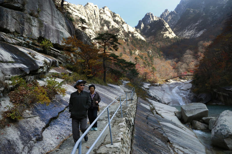FILE - In this Oct. 23, 2018, file photo, local tourists walk on the trail at Mount Kumgang, known as Diamond Mountain, in North Korea. North Korea on Friday, Nov. 15, 2019, said it issued an ultimatum to South Korea that it will tear down South Korean-made hotels and other facilities at the North's Diamond Mountain resort if the South continues to ignore its demands to come and clear them out.  (AP Photo/Dita Alangkara, File)