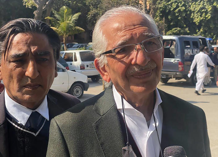 Mehmood A. Sheikh, right, a defense lawyer for British-born Pakistani Ahmed Omar Saeed Sheikh, who is charged in the 2002 murder of American journalist Daniel Pearl, talks to a journalists outside the Sindh High Court, in Karachi, Pakistan, Thursday, Dec. 24, 2020. The provincial court overturned a Supreme Court Decision that Sheikh should remain in custody during an appeal of his acquittal on charges he murdered Pearl. (AP Photo/Adil Jawad)