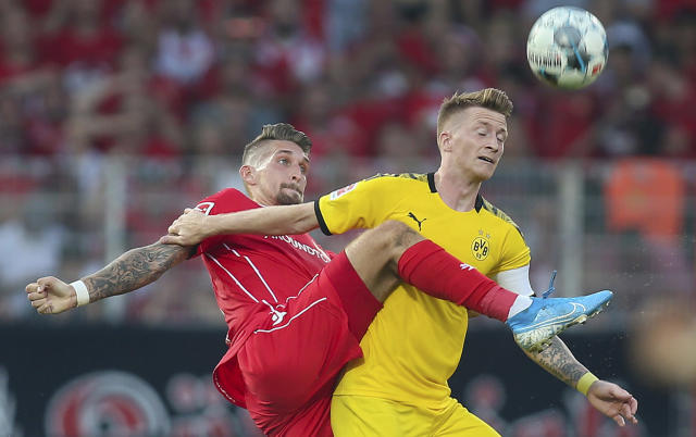 Berlin's Robert Andrich, left, and Marco Reus of Borussia Dortmund battle for the ball during a German Bundesliga soccer match between FC Union Berlin and Borussia Dortmund in Berlin, Germany, Saturday Aug. 31, 2019. (Andreas Gora/dpa via AP)
