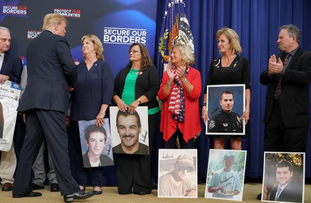 President Trump on Friday greets people holding posters of loved ones killed by undocumented immigrants. (Photo: Mandel NGAN/AFP/Getty Images)