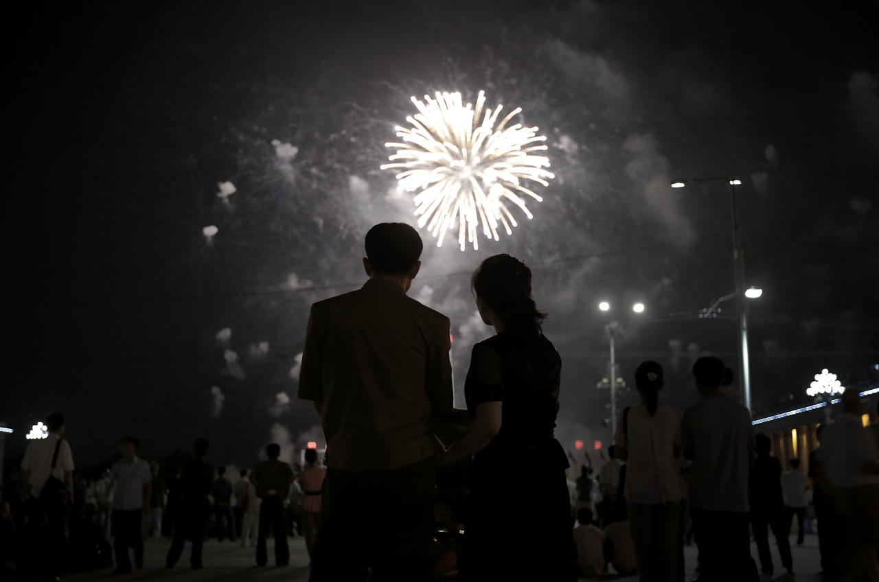 A North Korean couple is silhouetted against a fireworks explosion, Sunday, July 27, 2014 in central Pyongyang, North Korea. North Koreans gathered at Kim Il Sung Square to watch a fireworks display as part of celebrations for the 61st anniversary of the armistice that ended the Korean War.(AP Photo/Wong Maye-E)