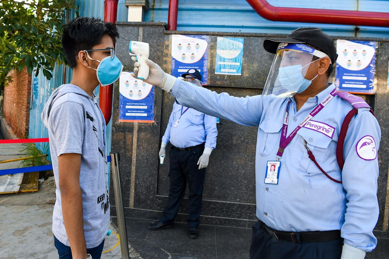 A student gets his temperature taken as he arrives at an examination centre for Joint Entrance Examination (JEE ) Main-2020, one of the most competitive entrance exams for entry to top national engineering colleges, in Noida on September 1, 2020. (Photo by PRAKASH SINGH/AFP via Getty Images)