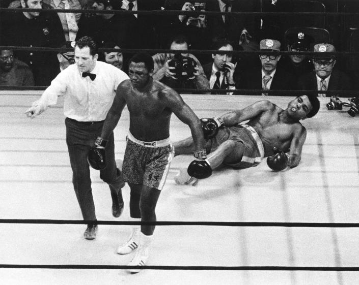 FILE - In this March 8, 1971, file photo, boxer Joe Frazier is directed to his corner by referee Arthur Marcante after knocking down Muhammad Ali during the 15th round of a title fight at Madison Square Garden in New York. Frazier won over Ali by decision. (AP Photo/File)