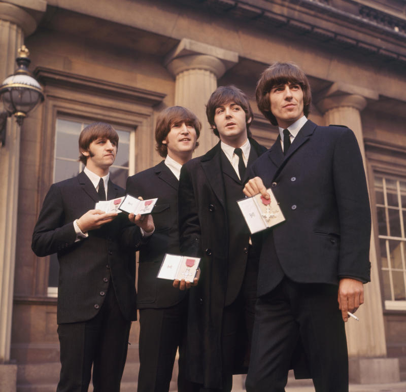 The Beatles showing their MBE Insignias in forecourt after receiving them from the Queen. L-R Ringo Starr, John Lennon, Paul McCartney and George Harrison.