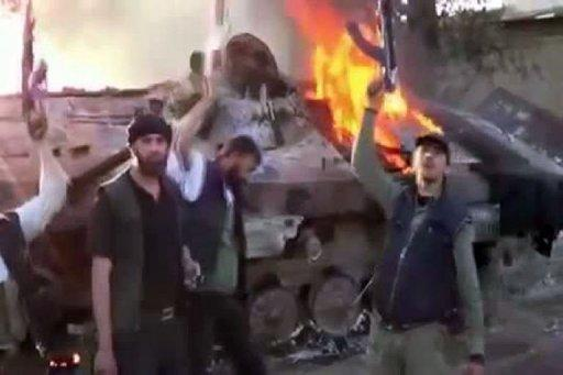 An image grab taken from a video uploaded on YouTube allegedly shows Syrian rebels raising their guns next to a burning tank after their confrontation with Syrian Army on the outskirts of Duma. President Bashar al-Assad has dismissed accusations his government had any role in the brutal Houla massacre, as he charged forces outside Syria of plotting to destroy the country
