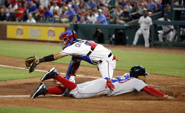 Boston Red Sox Mookie Betts, bottom, slides safely into home in front of Texas Rangers catcher Robinson Chirinos, top, during the seventh inning of a baseball game Saturday, May 5, 2018, in Arlington, Texas. (AP Photo/Michael Ainsworth)