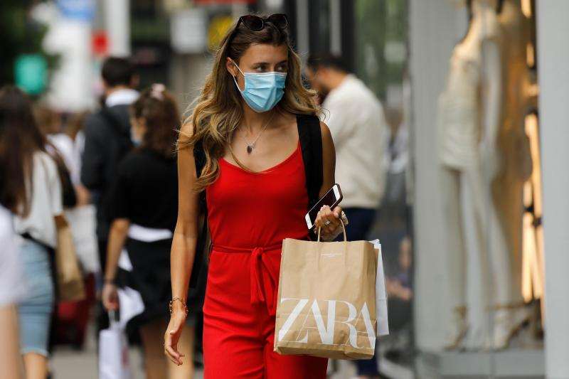 A shopper wears a face mask on Oxford Street om London on July 24, 2020, after wearing facemasks in shops and supermarkets became compulsory in England as a measure to combat the spread of the novel coronavirus. (Photo by Tolga AKMEN / AFP) (Photo by TOLGA AKMEN/AFP via Getty Images)