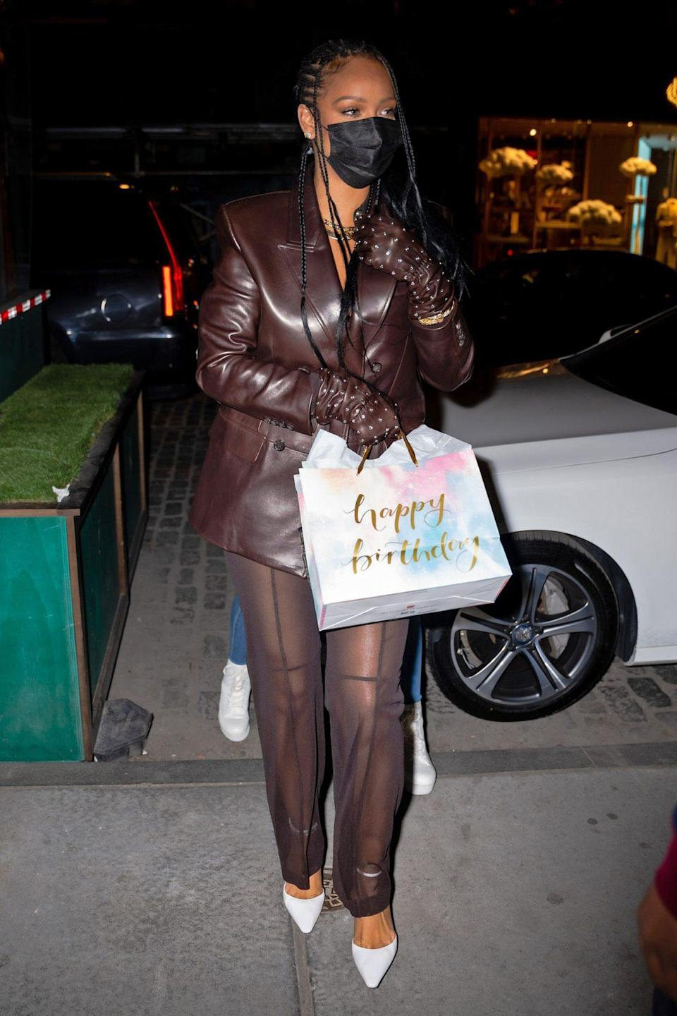<p>Rihanna holds onto a gift while arriving in N.Y.C.'s Meatpacking District on Monday. </p>