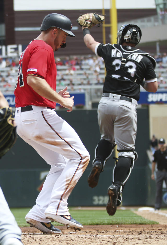 Minnesota Twins' C.J. Cron, left, scores on a single by Ehire Adrianza off Chicago White Sox pitcher Manny Banuelos in the fourth inning of a baseball game Saturday, May 25, 2019, in Minneapolis. Cron hit a two-run single in the fourth. (AP Photo/Jim Mone)