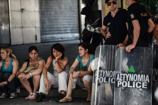 Police officers stand next to Greek municipal workers as they protest against the austerity measure on June 14