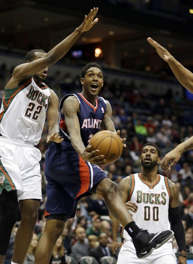 Atlanta Hawks' Louis Williams, middle, drives against Milwaukee Bucks' Khris Middleton (22) during the first half of an NBA basketball game Saturday, Jan. 25, 2014, in Milwaukee. (AP Photo/Jeffrey Phelps)