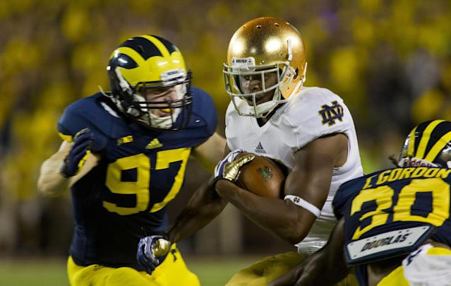 Michigan linebacker Brennen Beyer (97) tackles Notre Dame wide receiver C.J. Prosise in the first quarter of an NCAA college football game, in Ann Arbor, Mich., Saturday, Sept. 7, 2013. (AP Photo/Tony Ding)