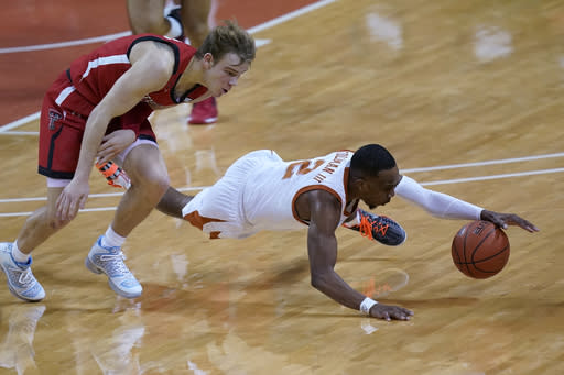 Texas guard Matt Coleman III (2) dives past Texas Tech guard Mac McClung (0) for a loose ball during the second half of an NCAA college basketball game Wednesday, Jan. 13, 2021, in Austin, Texas. (AP Photo/Eric Gay)