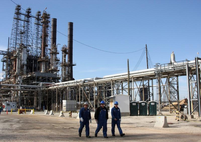Refinery workers walk inside the LyondellBasell oil refinery in Houston