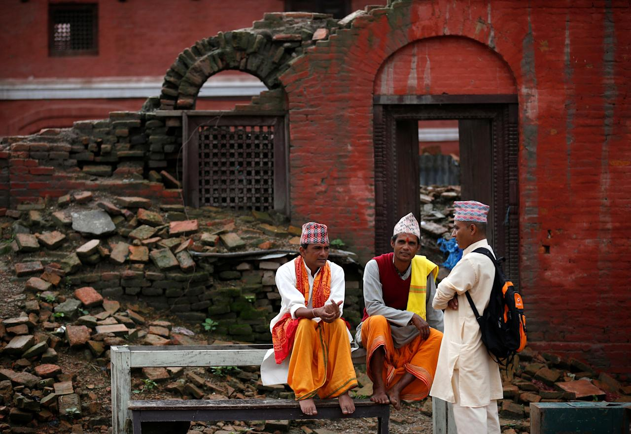Hindu priests rest near the building damaged during last yearÕs earthquake at the Pashupatinath temple during the Shrawan Sombar festival in Kathmandu, Nepal, July 18, 2016. The festival lasts for a month, during which devotees fast and worship Lord Shiva to pray for happiness for their families. REUTERS/Navesh Chitrakar