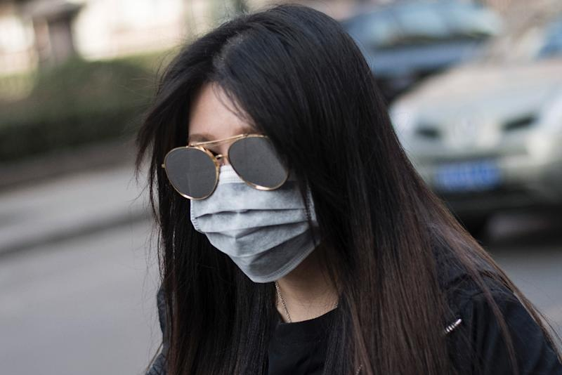 A woman wearing a face mask during a yellow alert for air pollution in Beijing on March 18, 2016