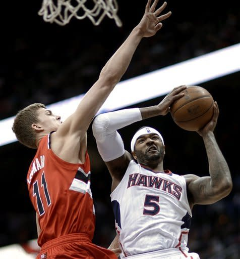 Atlanta Hawks' Josh Smith, right, is fouled by Portland Trail Blazers' Meyers Leonard while going up for shot in the second quarter of an NBA basketball game, Friday, March 22, 2013, in Atlanta. (AP Photo/David Goldman)