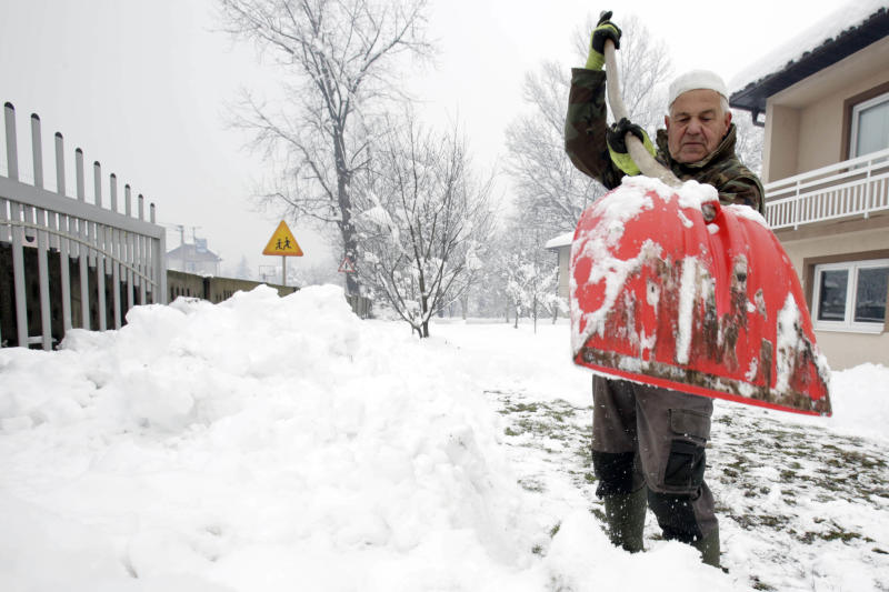 A Bosnian man shovels snow near Sarajevo, Bosnia, Monday, Dec. 17, 2018. Schools closed down for two days Monday in the central municipalities of Konjic and Jablanica, while trucks and heavy vehicles have been banned from some snow-covered roads. (AP Photo/Amel Emric)