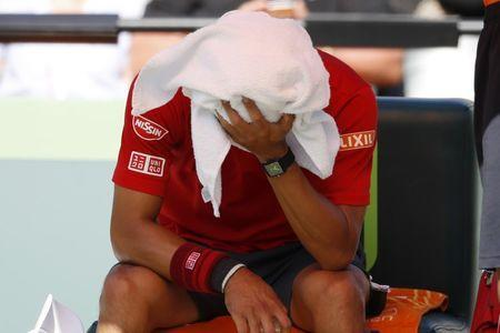Mar 29, 2017; Miami, FL, USA; Kei Nishikori of Japan holds a towel over his head during a changeover against Fabio Fognini of Italy (not pictured) on day nine of the 2017 Miami Open at Crandon Park Tennis Center. Fognini won 6-4, 6-2. Geoff Burke-USA TODAY Sports