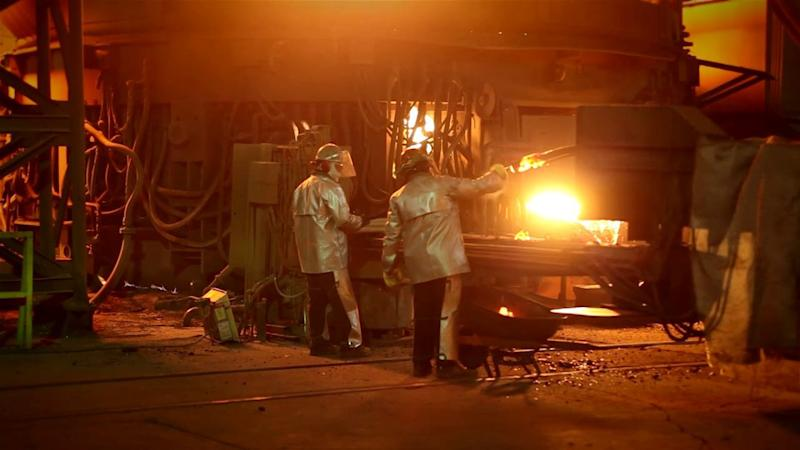Two workers wearing heat-resistant clothing near a blast furnace.