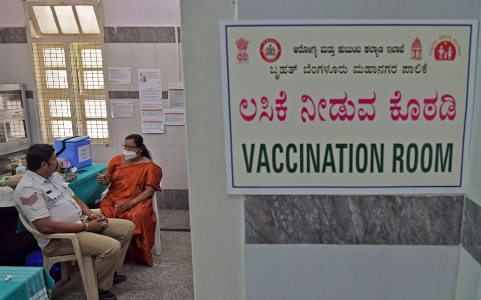 A medical worker preparing to give a Covid-19 jab to a policeman in Bangalore, India - Manjunath Kiran/AFP