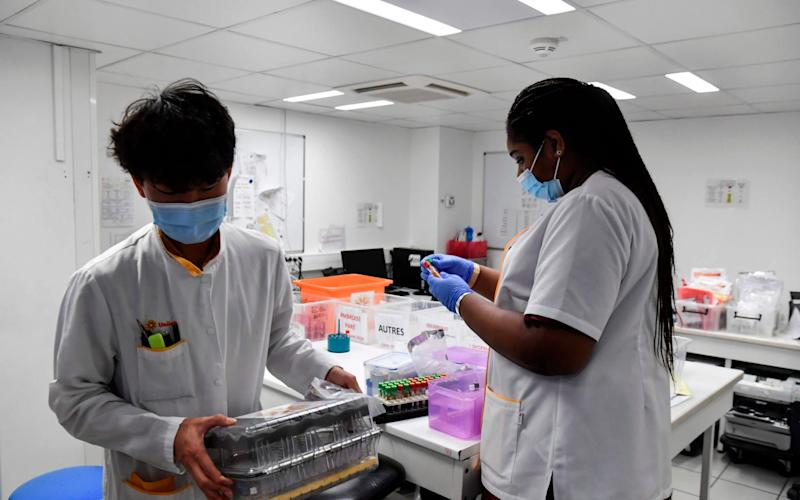Lab assistants receive samples for PCR tests to screen for Covid-19 at the Eylau Unilabs analysis laboratory in Neuilly-sur-Seine, outside Paris - ALAIN JOCARD/AFP