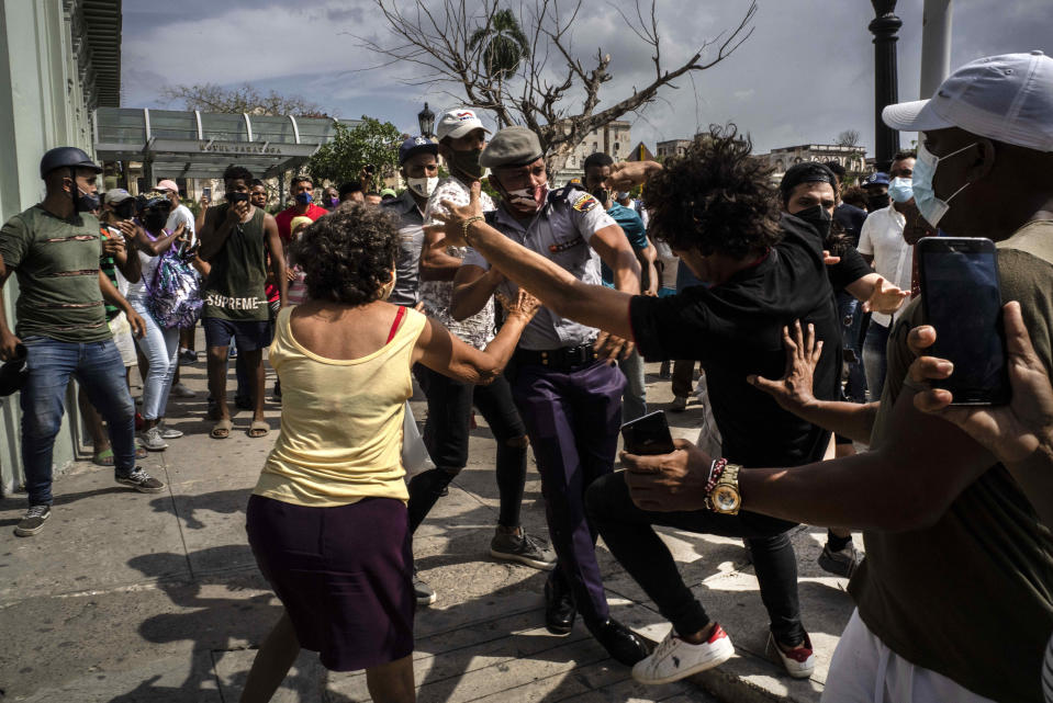 Police scuffle and detain an anti-government demonstrator during a protest in Havana, Cuba, Sunday July 11, 2021. Hundreds of demonstrators went out to the streets in several cities in Cuba to protest against ongoing food shortages and high prices of foodstuffs, amid the new coronavirus crisis. (AP Photo/Ramon Espinosa)