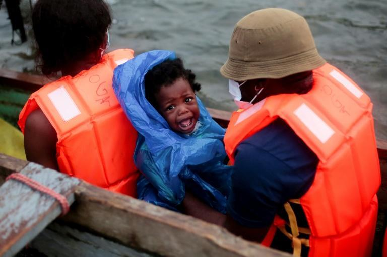 Migrants are given orange life vests and boarded onto canoes that take them along a river to a migrant shelter in Lajas Blancas