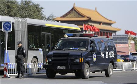 A policeman stands guard next to a police vehicle near Tiananmen Gate, in Beijing