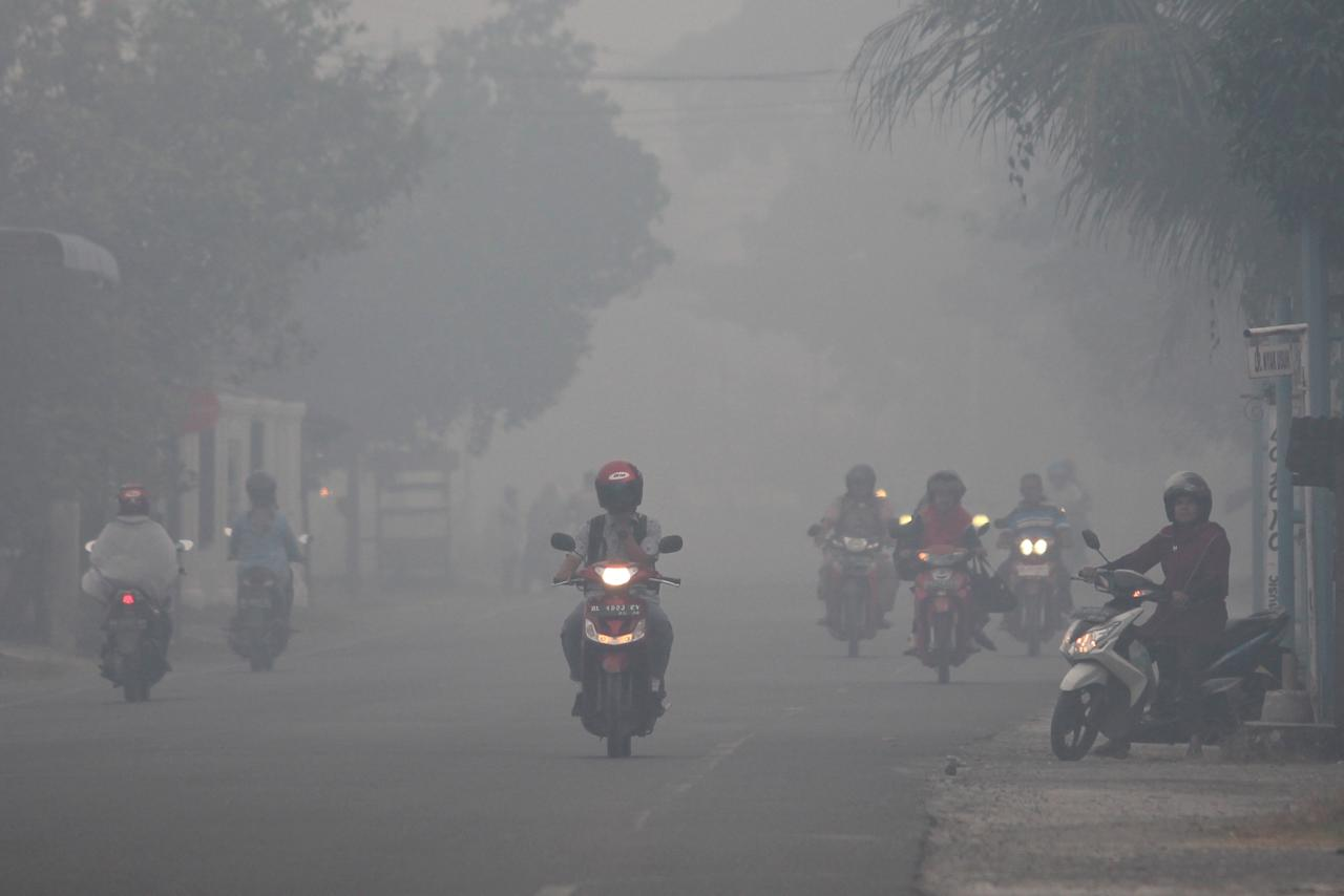 A resident drives a motorcycle through a haze produced by peatland fires at Suak Raya village in Aceh Barat, Aceh province, Indonesia July 27, 2017 in this photo taken by Antara Foto. Antara Foto/Syifa Yulinnas via REUTERS. ATTENTION EDITORS - THIS IMAGE WAS PROVIDED BY A THIRD PARTY. MANDATORY CREDIT. INDONESIA OUT. NO COMMERCIAL OR EDITORIAL SALES IN INDONESIA.
