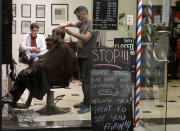 Cathedral Junction Barbers owner Conrad Fitz-Gerald cuts the hair of a customer just past midnight in Christchurch, New Zealand, Thursday, May 14, 2020. New Zealand lifted most of its remaining lockdown restrictions from midnight Wednesday (noon Weds. GMT) as the country prepares for a new normal. Malls, retail stores and restaurants will reopen and many people will return to their workplaces. (AP Photo/Mark Baker)
