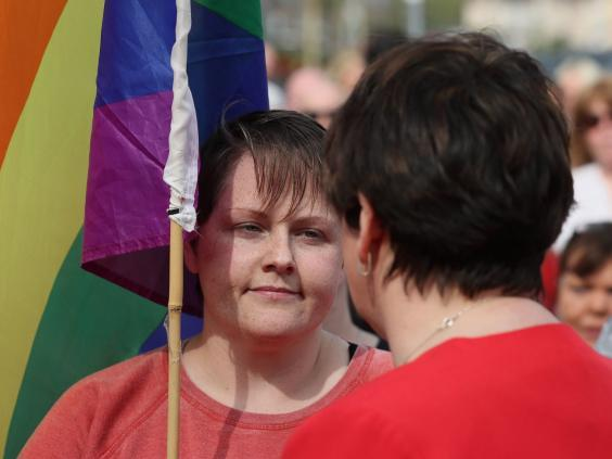 DUP leader Arlene Foster speaks with Sara Canning (left), the partner of journalist Lyra McKee, at a vigil (PA)