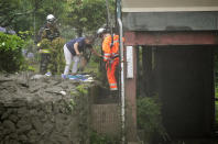Firefighters help a resident evacuate after a mudslide at the Izusan district in Atami, west of Tokyo, Saturday, July 3, 2021, following heavy rains in the area. The mudslide carrying a deluge of black water and debris crashed into rows of houses in the town following heavy rains on Saturday, leaving multiple people missing, officials said. (Kyodo News via AP)